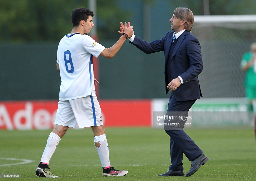 FC Internazionale Milano Juvenile coach Stefano Vecchi (R) celebrates a victory with his player Mattia Bonetto (L) at the end of the juvenile match between AC Milan and FC Internazionale at Centro Sportivo Giuriati on April 29, 2016 in Milan, Italy.