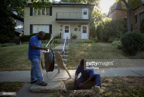 US Internet Corp linemen Hughie Smith left and Keanu Smith feed fiber optic internet cable into underground tubing during installation in Minneapolis...