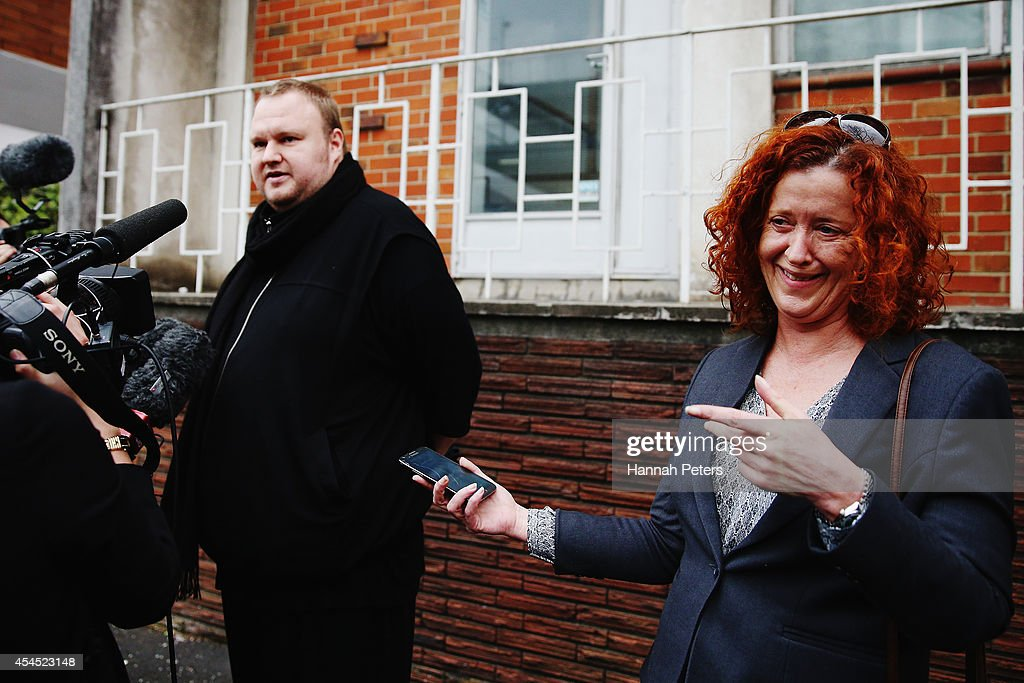 Internet MANA press secretary Pam Corkery listens as founder Kim Dotcom speaks to the media after placing his advance vote at Liston House on September 3, 2014 in Auckland, New Zealand. The Internet MANA party will go head to head with other parties at the general election on 20 September 2014.