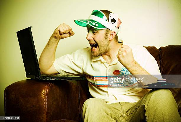 Internet poker player with visor cheering at laptop