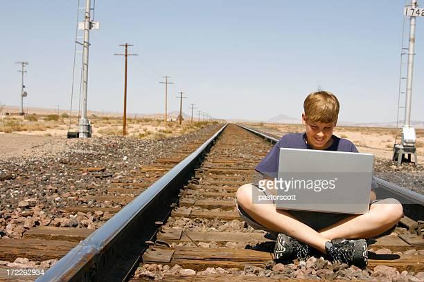 Internet security danger social media boy train laptop downloading facebook