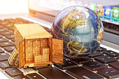 Global freight transportation business, cargo container with cardboard boxes and Earth globe on laptop
