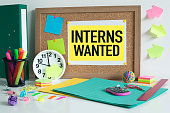 Interns wanted sign note on cork bulletin board.