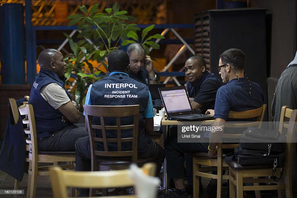 Interpol agents sit at a coffeshop near the Westgate Shopping Centre on September 28, 2013 in Nairobi, Kenya. Officials begun the task of forensic probing the Westgate shopping mall following a four-day siege that killed at least 67 civilians and police and was claimed by the Somali militant group al Shabaab.