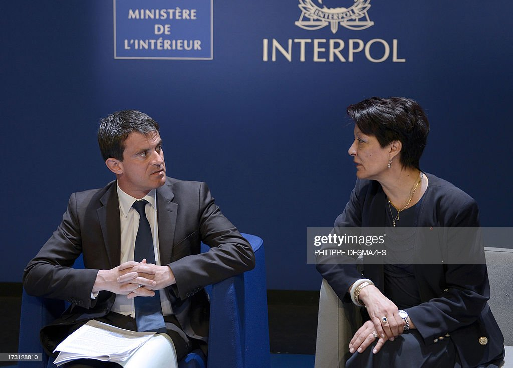 Interpol President Mireille Ballestrazzi (R) talks with French Interior minister Manuel Valls during the opening plenary session of an Interpol international forum on Technology Against Crime (TAC) on July 8, 2013, in Lyon, southeastern France.