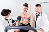 Athlete does a cardiac stress test in a medical study, monitored by the doctor and nurse