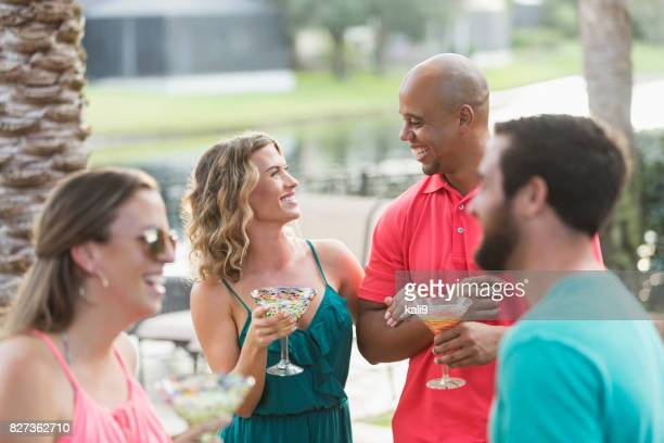 Interracial couple at party, drinking cocktails