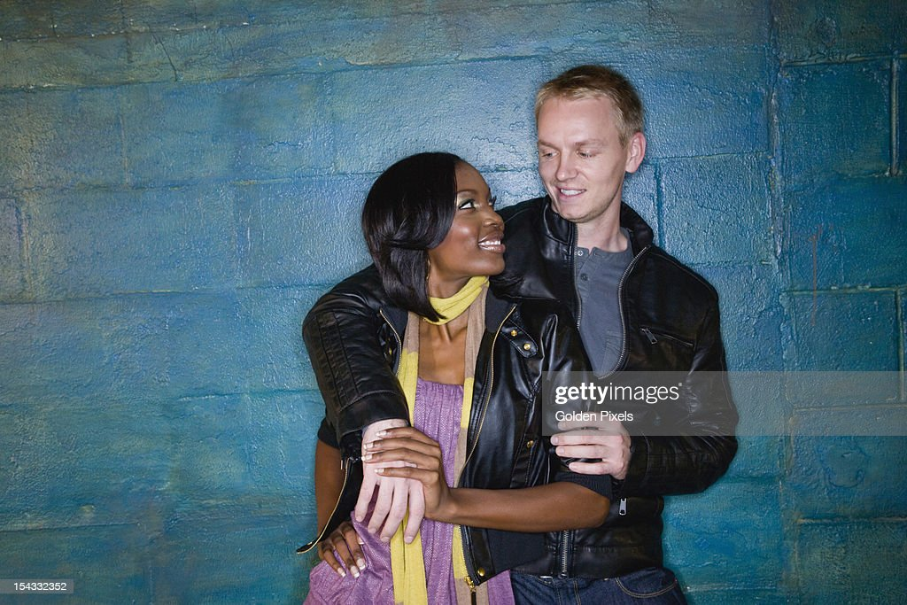 Interracial couple leaning against grungy blue wall : Stock Photo