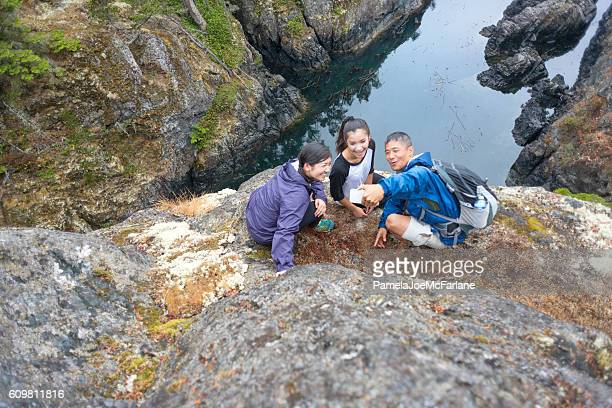 Interracial Family Taking Selfie While Hiking along Rugged Ocean Cliff