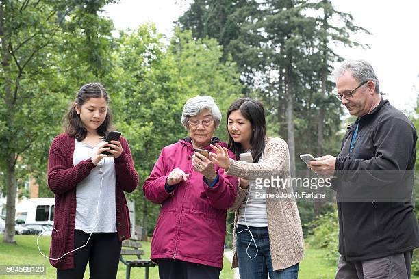Interracial, Multi-Generational Family Playing Smartphone Augmented Reality Game in Park