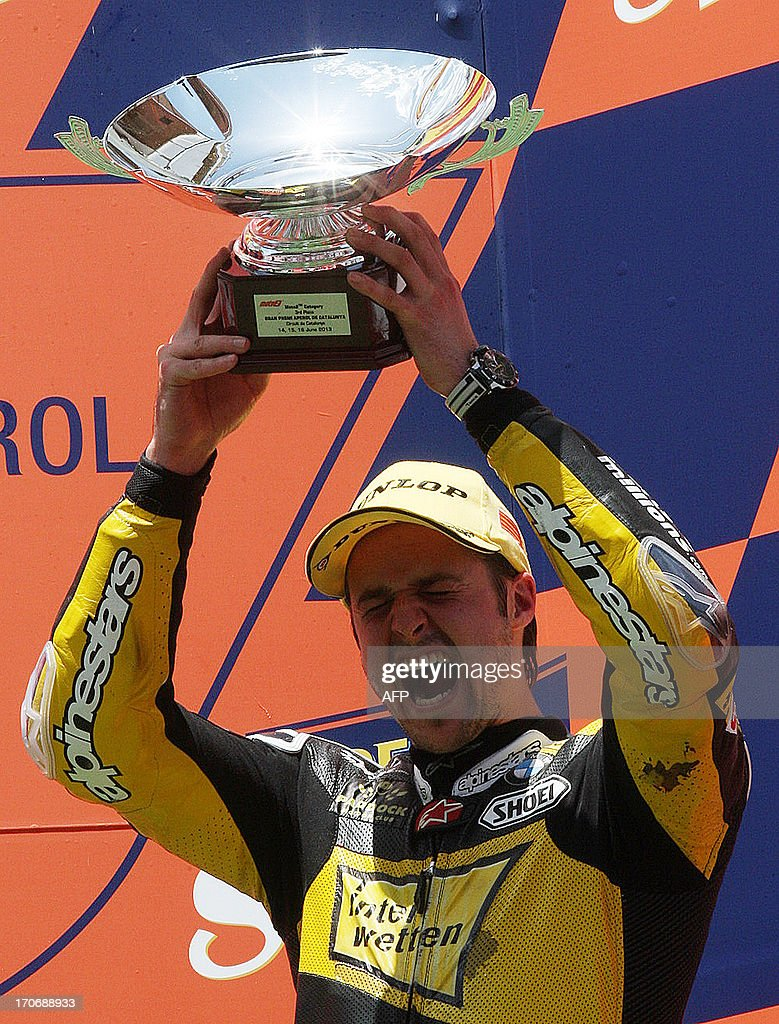 Interwetten Paddock Racing's Swiss rider Thomas Luthi celebrates his third place on the podium of the Moto2 race of the Catalunya Grand Prix at the Catalunya racetrack in Montmelo, near Barcelona, on June 16, 2013. Tuenti HP 40's Spanish rider Pol Espargaro won the race ahead of Tuenti HP 40's Spanish rider Esteve Rabat and Interwetten Paddock Racing's Swiss rider Thomas Luthi.