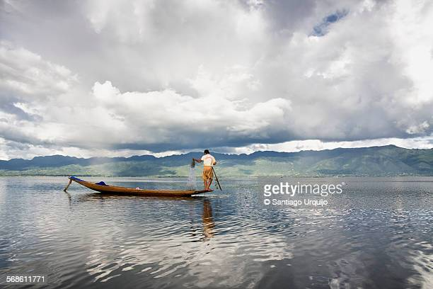 Intha fisherman casting a fishing net in Inle Lake