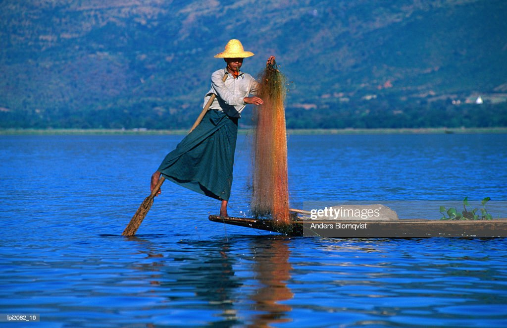 Intha fisherman tending to nets and rowing in traditional manner with legs, Inle Lake, Shan State, Myanmar (Burma), South-East Asia : Stock Photo