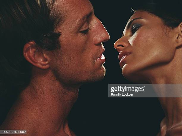 Intimate couple leaning into kiss against black background, close-up