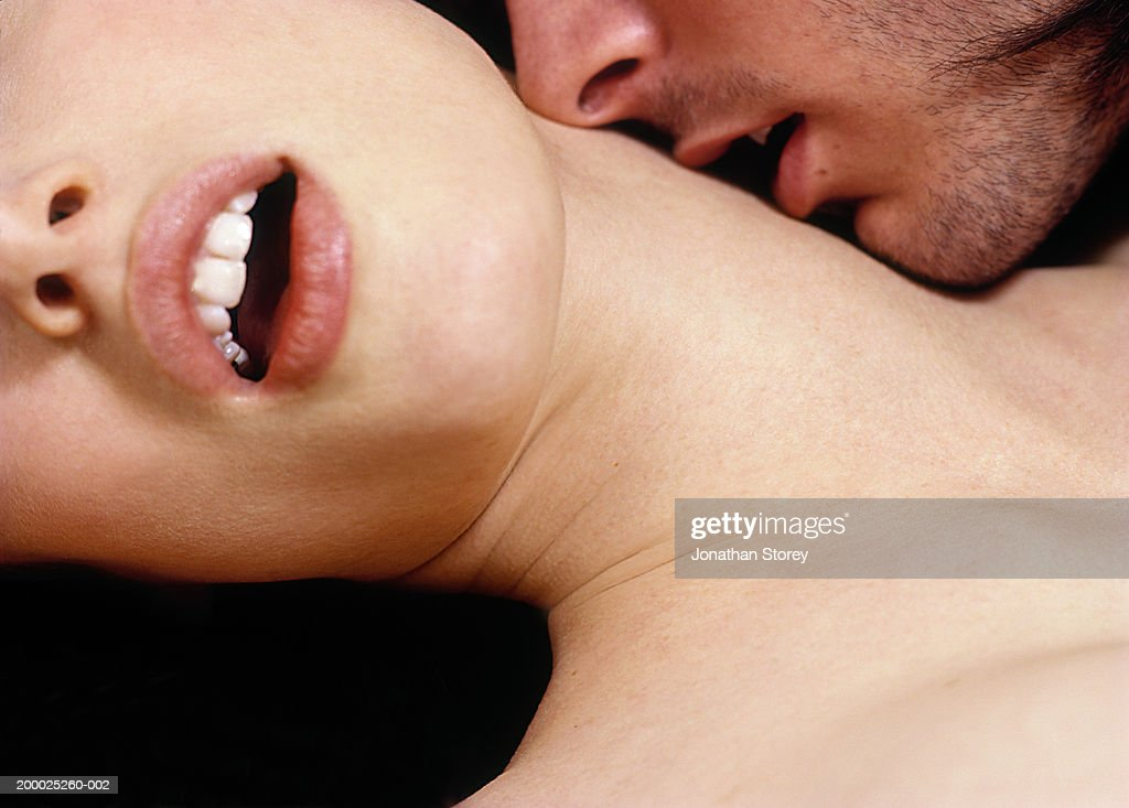 Intimate couple, man kissing woman's neck, close-up : Stock Photo