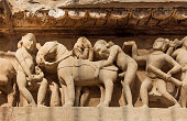 Intimate life of ancient people on stone relief on wall of Khajuraho temple, India. UNESCO Heritage site, built between 950 and 1150 in India, belong to Hinduism and Jainism.