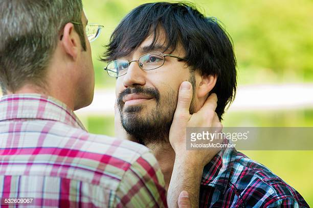 Intimate moment between two gay men on a park date