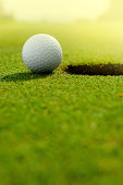 Close up of a golf ball close to the hole