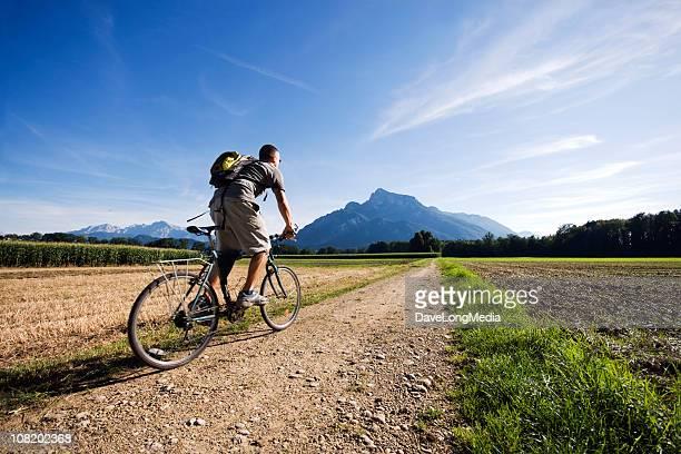 Into the Wild - Mountain Biker Riding Toward Mountains