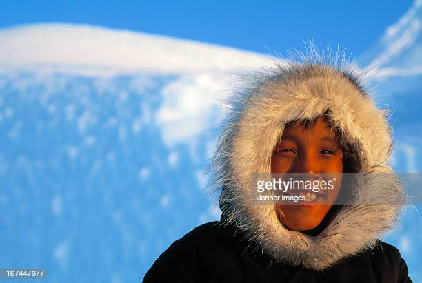 Inuit, Eskimo boy in front of ice berg, Canada.