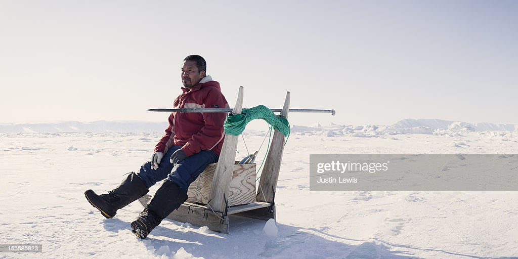 Inuit fisherman rests on sled while ice fishing : Stock Photo