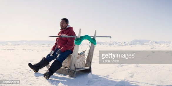 Inuit fisherman rests on sled while ice fishing : Stock-Foto