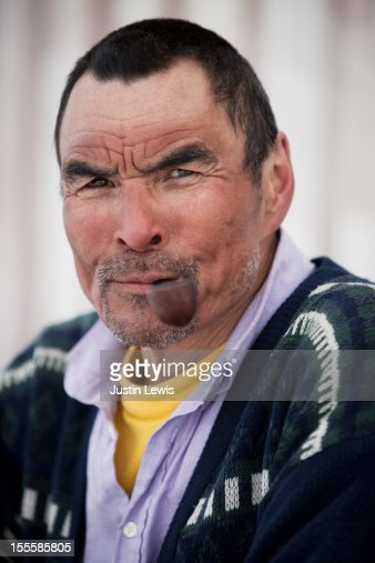 Inuit hunter portrait - smiles and smokes pipe : Stock Photo