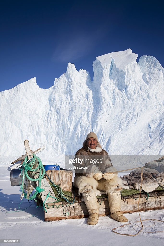 Inuit male in fur sits on sled in front of iceberg : Stockfoto