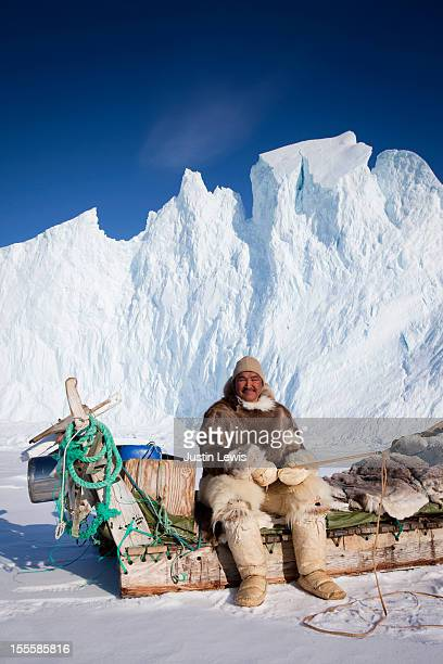 Inuit male in fur sits on sled in front of iceberg