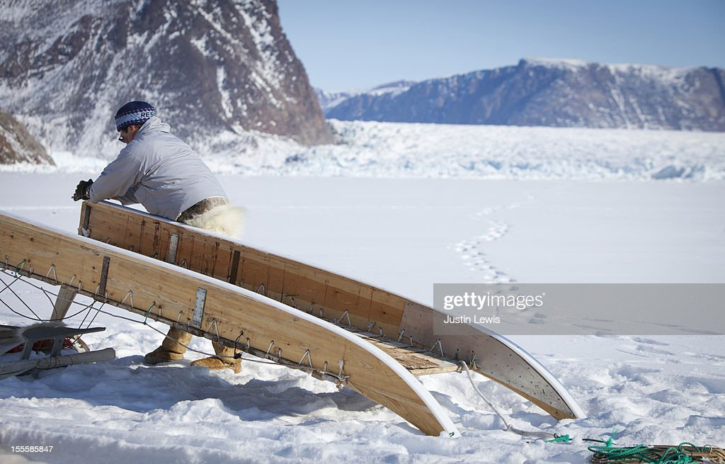 Inuit man cleans runners on sled by glacier head : Stock Photo