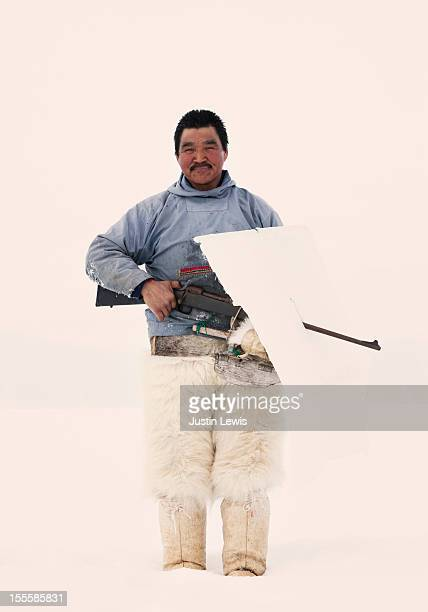 Inuit man hold hunting gun in polar bear pants