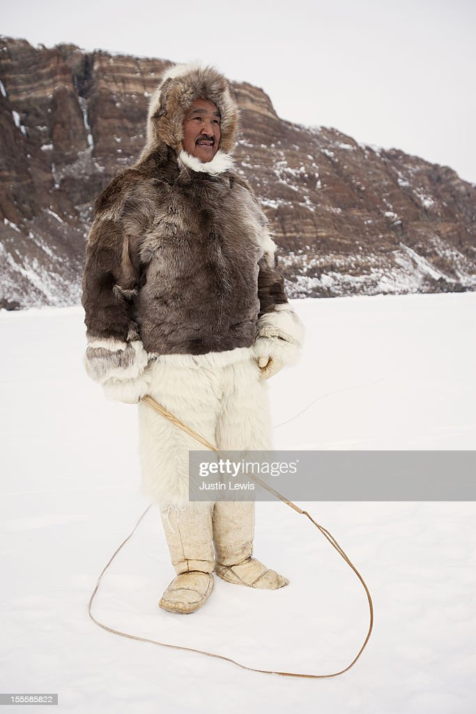 Inuit man in fur jacket and pants & dog sled whip : Stock Photo