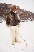Inuit man in fur jacket and pants & dog sled whip