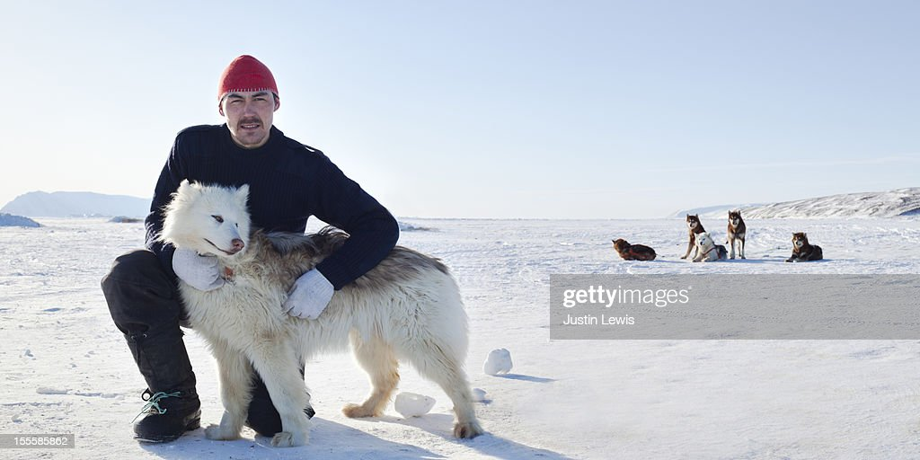 Inuit man poses with arctic dog on sea ice : Stock Photo