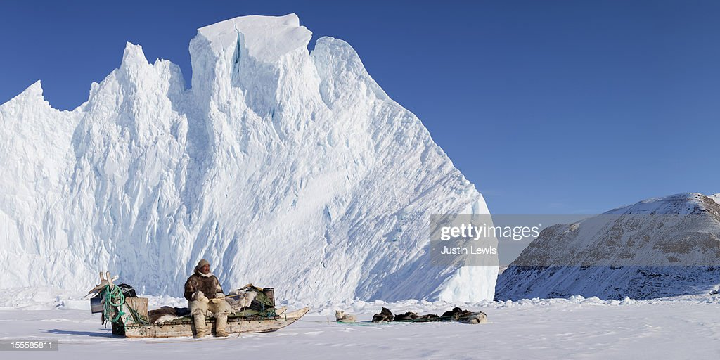 Inuit man sits on his sled with dogs and iceberg : Stock Photo