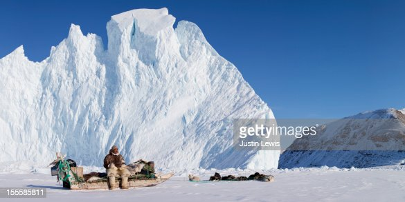 Inuit man sits on his sled with dogs and iceberg : Stockfoto