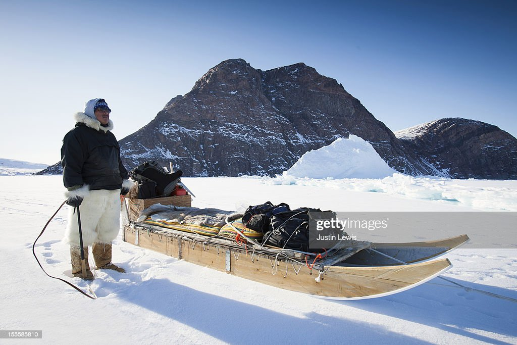 Inuit man stands next to dog sled on sea ice : Stock Photo