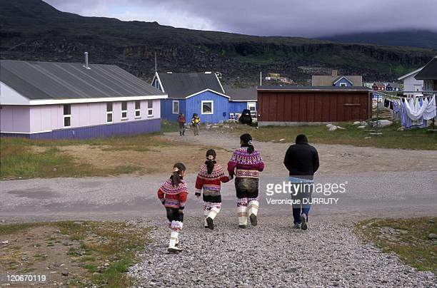 Inuit mother and girls wearing the traditional costume embroidered with colored pearls in Qeqertarsuaq Greenland in 2010 Qeqertarsuaq is a port and...