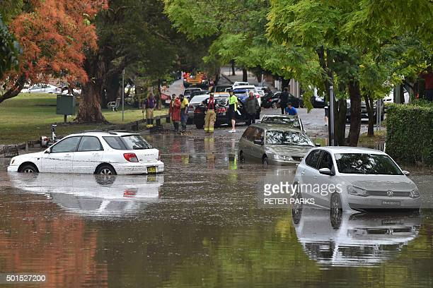 Inundated cars are seen on a flooded street after a storm in the eastern suburbs of Sydney on December 16 2015 Sydney was smashed by a tornadolike...