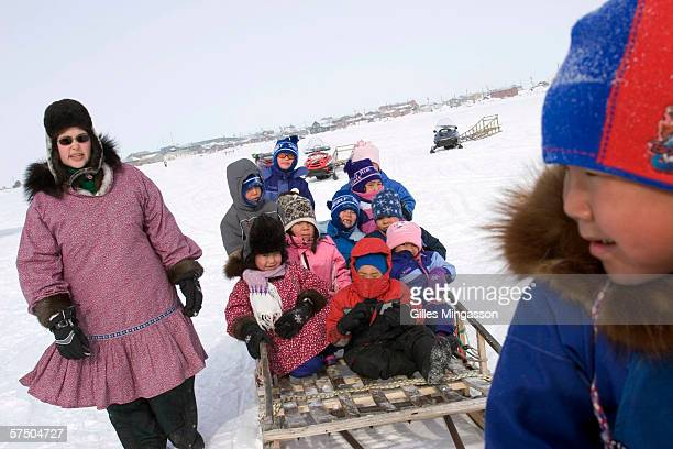 Inupiat Eskimo kindergardeners on a field trip to a local dogsled race get ready to head back to class with their teacher on a sled pulled by the...