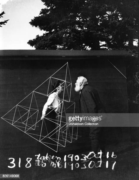 Inventor Alexander Graham Bell poses for a portrait with his wife Mabel Hubbard Gardiner Bell inside the framework of a tetrahedral kite in circa 1903
