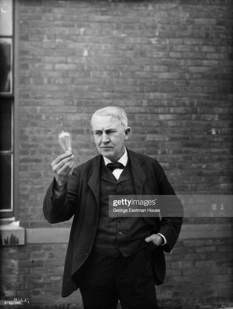 Inventor and physicist Thomas Alva Edison (1847 - 1931) looking at a lightbulb