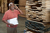 Inventory Manager on Cell Phone in Lumber Warehouse