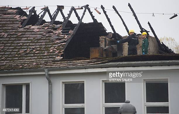 Investigation officers work in the attic of a burned house that was to be a refugee home in Trassenheide northern Germany on November 15 2015 For...