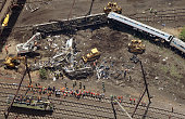 Investigators and first responders work near the wreckage of Amtrak Northeast Regional Train 188 from Washington to New York that derailed yesterday...