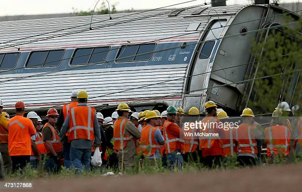 Investigators and first responders work near the wreckage of an Amtrak passenger train carrying more than 200 passengers from Washington DC to New...