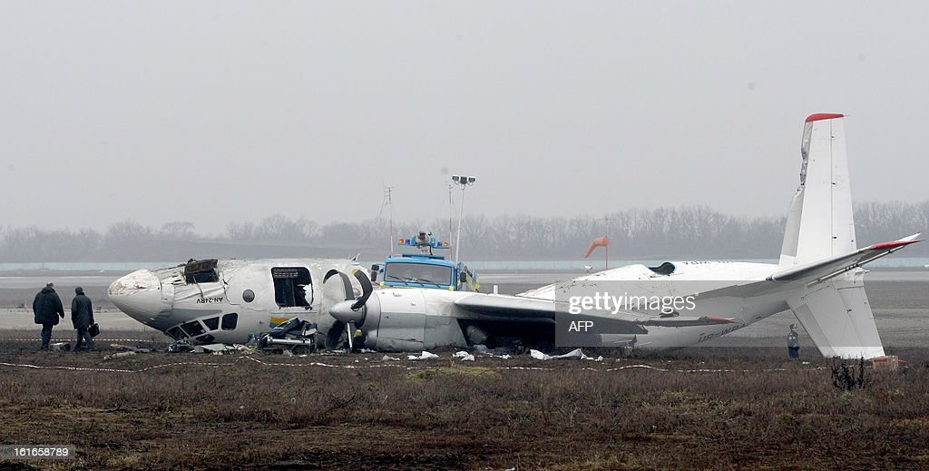 Investigators and police officers stand near the debris of an An-24 plane which made an emergency landing in the eastern Ukraine city of Donetsk, on February 14, 2013. At least four people died yesterday when an Antonov An-24 passenger turboprop plane with dozens of football fans on board made an emergency landing in Donetsk, officials said. The passengers were on their way to Donetsk to watch a match between Shakhtar Donetsk and Borussia Dortmund. AFP PHOTO / Alexander KHUDOTEPLY