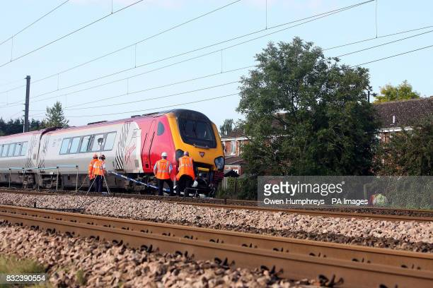 Investigators and railway officials examine a train which collided with a car late Monday evening on the East Coast Main Line in the village of...