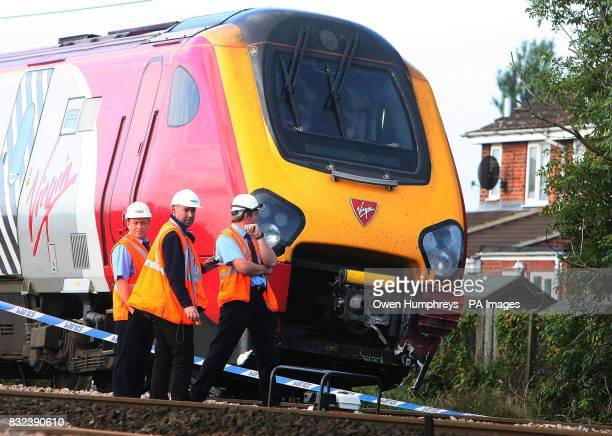 Investigators and railway officials stand by a train which collided with a car late Monday evening on the East Coast Main Line in the village of...