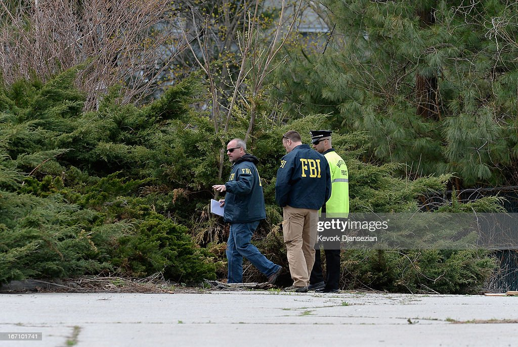 FBI investigators and Watertown Police officer walk in parking lot as they investigate the shooting scene near the boat where bombing suspect was hiding from police on Franklin Street on April 20, 2013 in Watertown, Massachusetts. A manhunt for Dzhokhar A. Tsarnaev, 19, a suspect in the Boston Marathon bombing ended after he was apprehended on a boat parked on a residential property in Watertown, Massachusetts. His brother Tamerlan Tsarnaev, 26, the other suspect, was shot and killed after a car chase and shootout with police. The bombing, on April 15 at the finish line of the marathon, killed three people and wounded at least 170
